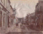 City street scene showing people walking, jinrikishas (rickshaws), and horse drawn carts outside...