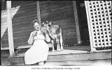 Mary Cruse with calf on porch, Bellevue, ca. 1920