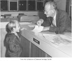 Fred Herman talking to boy in planning office, Bellevue, ca. 1970