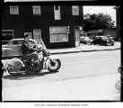 Man riding motorcycle on Leary Way, Redmond, June 9, 1956