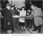 Inez Green cutting ribbon at Meydenbauer Bay Bridge dedication, Bellevue, February 11, 1950