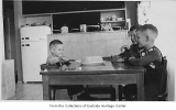 Three boys at table inside Hook home, Norwood Village, June 1954