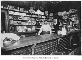 Man behind counter in store, ca. 1920