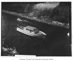 Bob Cat III, a gasoline powered yacht, in a canal, n.d.