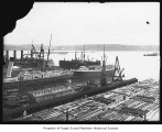 Moran Brothers Shipyard, bird's-eye view, with ships moored at the pier and lumber ready to load,...