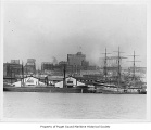 Mackinaw, a steam freighter, and a sailing ship moored at piers 9 and 10 on the Seattle...