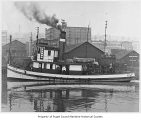 Elf, a steam tugboat, in a harbor in Tacoma, n.d.