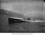 Seattle Spirit, a gasoline powered motorboat, at sea with a hill in the background, n.d.