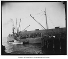 Horace X. Baxter, a lumber carrying steamer, at a pier with another steamer Wanick and a smaller...