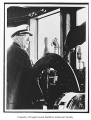 Captain L. Smiley at the helm of the tug Gleaner, n.d.