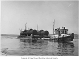 Henrietta Foss, a diesel powered tugboat, at sea and towing a barge, n.d.