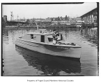 Fellowship-Too, a gasoline powered cruiser, in a canal with a photographer on the bow, 1941