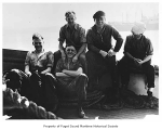 Captain Ray Quinn sitting with crew members of the Neptune, n.d.