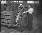 Woman with metal finishing machine, Seattle, 1945