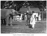 Roald Amundsen and Chukchi girls with elephant at Woodland Park, Seattle, 1921