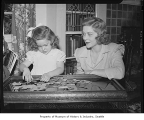 Mrs. Clay Johnson watching daughter Betsy work on a puzzle, possibly in Seattle, 1945