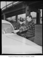 Man showing pitted windshield to police officer, Seattle, 1954