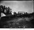 Truck towing crashed plane, June 24, 1929