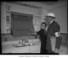 Civil Defense officer with a woman inside a house and boarding a window, possibly in Seattle, 1943