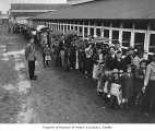 Internees lined up in the rain at Camp Harmony, Puyallup, 1942