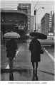 Pedestrians with umbrellas in downtown Seattle, 1970