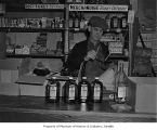 Man working in liquor store, Seattle, 1955