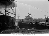 Foss tugs shooting water at Ballard mill fire, Seattle, 1969