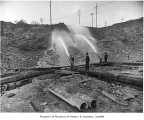 Workers using water hoses to regrade Denny Hill, Seattle, ca. 1909