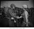 Woman shaking hands with soldier as troops board ship, Seattle, 1945