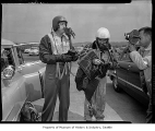 Boeing test pilots Tex Johnston and Dix Loesch being filmed in a parking lot, 1954