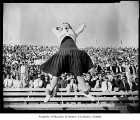 Husky cheerleader Dorothy Provine leads yell during a football game at Husky Stadium, Seattle,...