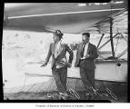 Will Rogers and Wiley Post beside their airplane and looking away from the camera, Renton Field,...