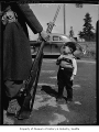 Japanese American boy standing near a soldier with a rifle, possibly in Seattle, 1942