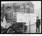 Jitney bus driver with sign criticizing streetcar system, Seattle, 1918