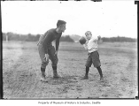 University of Washington football player Roy Eckman coaching boy, Seattle, 1923
