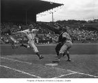 Dick Gyselman playing for the Seattle Rainiers and running toward first base at Sick's stadium,...