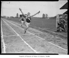 Runner crossing the finish line during a high school track meet relay race at Husky Stadium,...