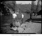 Opening day of fishing season showing men fishing in a stream, possibly in Seattle, 1963