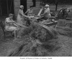 Four women processing flax outside a home near Lake Sammamish, 1943