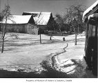 Man walking on snowy farm, Enumclaw, 1972