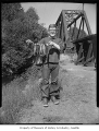 Opening day of fishing season showing a boy holding string of fish near a bridge, possibly in...