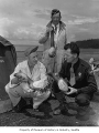 Stanley Kopp, Cliff Skroudal, and Pat White holding geoduck clams on a Washington beach, 1948