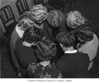 Women in a circle posing for a view of their hairstyles from above, possibly in Seattle, 1940