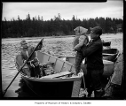 Opening day of trout fishing season showing a man helping children board a boat, probably in...