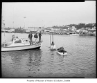 Coast Guard boat on Lake Union with men working on a buoy, Seattle, 1962