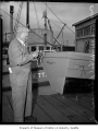 Halibut fisherman Elias Gumlam ties rope on boat, Fishermen's Terminal, Seattle, July 1, 1947