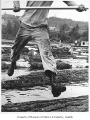 Man jumping floating logs, Kenmore, 1952