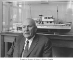 Horace W. McCurdy in front of a model of his yacht 'Blue Peter,' probably in Seattle, 1967