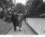 James W. Maxwell and wife walking along a sidewalk, possibly in Seattle, 1938