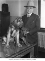 Sheriff Bill Severyns in an office with bloodhounds on a desk, possibly in Seattle, 1938